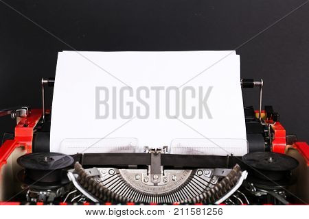 A top view of a red vintage typewriter with a white blank sheet of paper. Concern work, business.