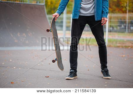 Close-up of a skateboarder's foot in an autumn skate park. A skateboarder is holding a skateboard. The concept of sport.