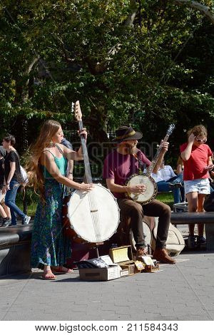 NEW YORK - OCTOBER 22 2017: Two street musicians perform as the duo Coyote & Crow playing the cello banjo and banjo for tourists in Washington Square Park Greenwich Village Manhattan.