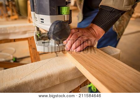 Man processing wood with router or moulding machine in a woodworking shop