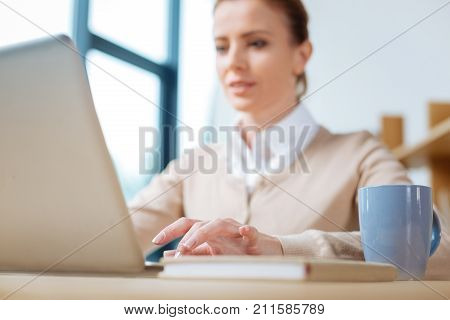 Talented secretary. Close up of pleasant busy woman working with a laptop while sitting at the table and being concentrated