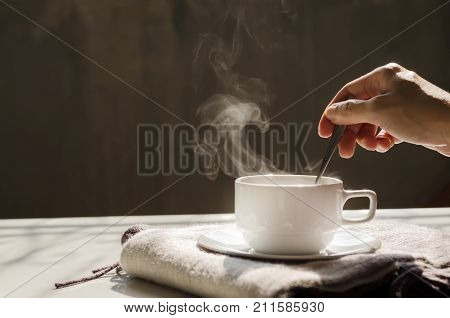 Background of hot black coffee in white ceramic cup and saucer over cozy wool scarf stirring for steam by woman or female right hand over dark background with warm morning light and copy space for text or logo insertion