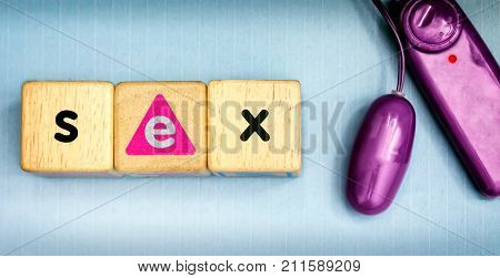 Wooden Dice Spells SEX next to a Purple Vibrator