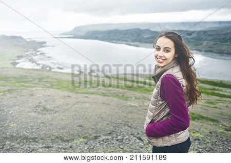 Girl in warm clothing observing surroundings on background of mountains and sea of Iceland.