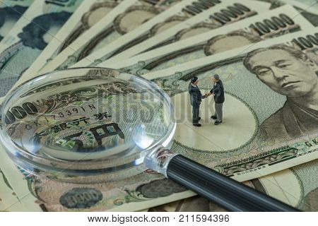 Business transparency or cheating concept as miniature figure businessmen handshaking and standing on pile of japanese yen banknotes with magnifying glass.