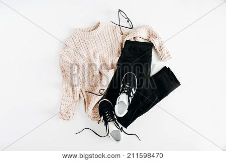 Fashion winter women clothes look on white background. Flat lay top view. Sweater sneakers jeans and glasses.