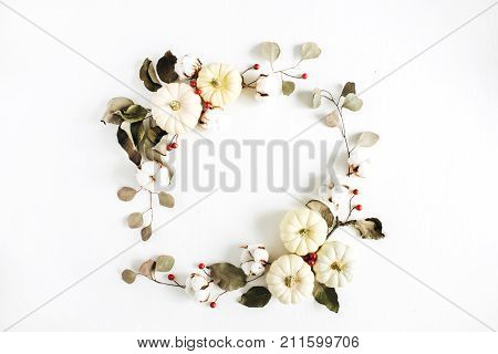 Wreath frame made of white pumpkins red berries and eucalyptus branches on white background. Flat lay top view autumn fall composition.