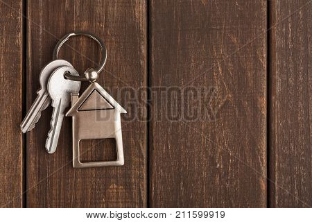 Two steel keys with house shaped trinklet on keyring on brown rustic wooden background with copy space. Home key, safety, security, real estate and rent concept, top view