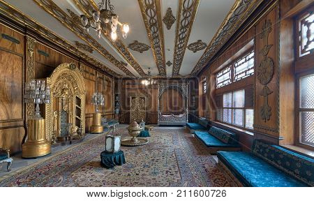 Cairo Egypt - October 21 2017: Manial Palace of Prince Mohammed Ali Tawfik. Residence of prince's mother with golden ornate niche silver bed golden wardrobe blue couches ornate wooden wall and ceiling