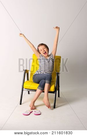 Tired sleepy girl yawning with a stretch while sitting on chair over light background. Shot of a young girl stretching her arms and yawning.