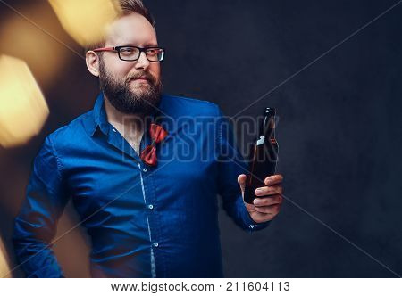 Fat male in eyeglasses dressed in a shirt with bow tie drinks craft beer from a bottle.