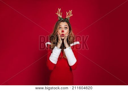 Portrait of a surprised pretty girl wearing christmas deer costume while holding her hands at face and looking at camera isolated over red background