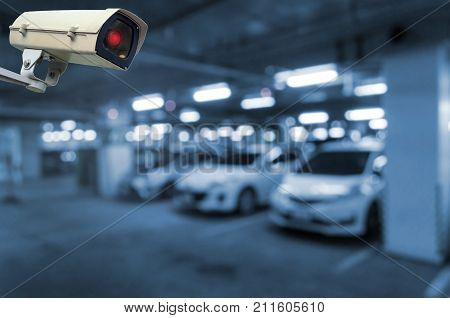 CCTV security indoor camera system operating in underground car parking garage area intelligent car parking surveillance security and safety technology concept blue color tone