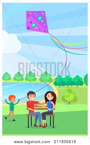 Young couple sitting on wooden bench in public park and running little boy that flies kite near lake on background. Relaxation outdoors in summer