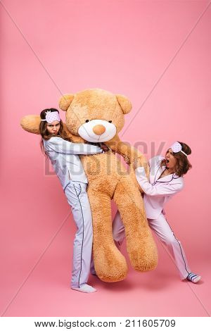 Image of two displeased friends women in pajamas isolated over pink background can't divide big teddy toy bear.