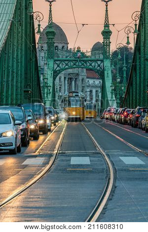 BUDAPEST HUNGARY - SEPTEMBER 27, 2017: Traffic on Liberty bridge. Evening traffic and trams on the iconic Liberty bridge in Budapest Hungary on September 27, 2017.