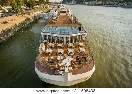 BUDAPEST HUNGARY - SEPTEMBER 26, 2017: Canal boat on a river. Front view of the company Viking Cruises canal boat on the Danube river in Budapest Hungary on September 26, 2017. People on board and ashore.
