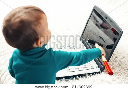A Little Boy With A Hammer Smashes The Laptop