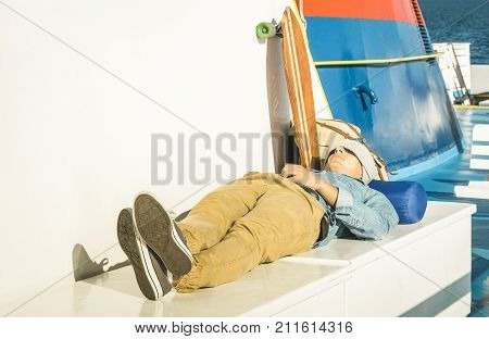 Young hipster man having rest on ferry boat passage holding smartphone - Modern concept of inspired freedom and wander lifestyle - Cheap travel backpacking around the world - Warm afternoon filter
