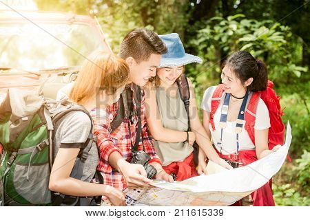 Hiking - hikers looking at map. Couple or friends navigating together smiling happy during camping travel hike outdoors in forest. Young mixed race asian woman and man. Hiking travel concept.