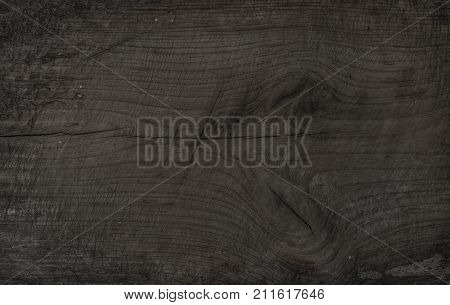 Old rustic discolored wooden board. Dark gray wooden texture, wallpaper and background. Brown-gray texture, surface and wallpaper