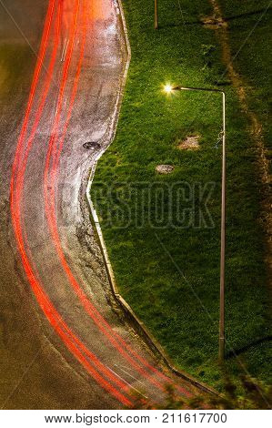 Aerial view of the luminous streetlight and the road with light trails after rain at night
