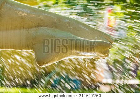 Feet of sculpture Khosta on the background of falling drops in fountain closeup Sochi Russia