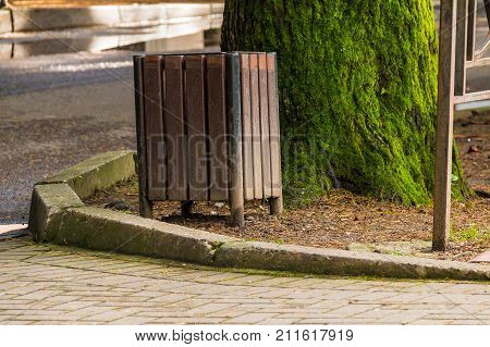Wooden trash can near the tree trunk on the lawn closeup