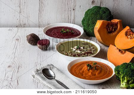 Different vegan food. Colorful vegetables cream soups and ingredients for soup. Healthy eating, dieting, vegetarian kitchen and cooking concept