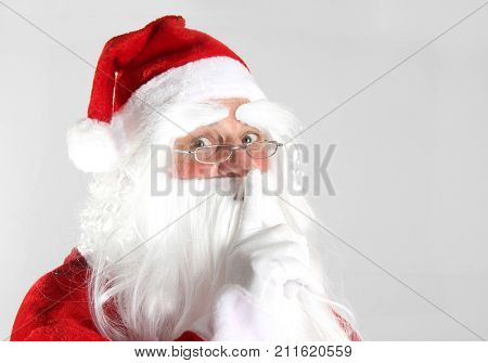 Christmas Santa Claus holding a finger to keep quiet.
