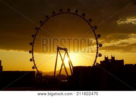 LAS VEGAS - JUNE 29 2015 - The High Roller Wheel light up at as sunrise comes through the wheel at dawn at the center of the Las Vegas Strip on June 29 2015 in Las Vegas. The High Roller is the world's largest observation wheel.