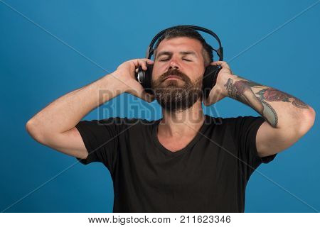 Man Holds Headphones On Blue Background. Pleasure, Music And Lifestyle