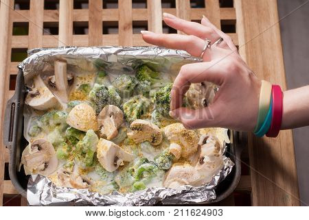 female hands, Broccoli, mushrooms in the sauce. top view, vegetarian dishes