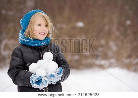 Portrait of adorable little kid boy with long blond hair holding snowballs and playing with them outdoors. Child with blue scarf and hat walking and having fun on a windy winter day. poster