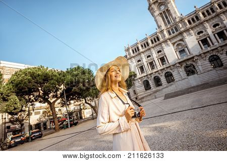 Portrait of a young woman tourist in sunhat standing with photo camera in front of the city hall building during the morning light in Porto, Portugal