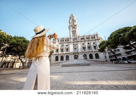 Young woman tourist photographing with phone the city hall building during the morning light in Porto, Portugal