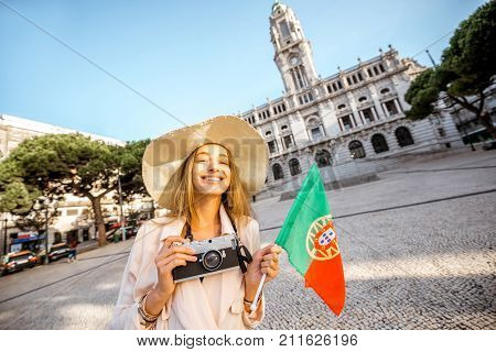 Portrait of a young woman tourist in sunhat standing with portuguese flag in front of the city hall building during the morning light in Porto, Portugal