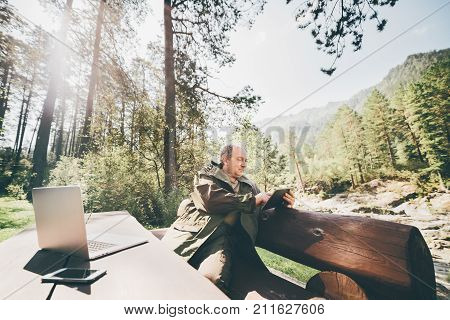 Mature forest warden is sitting on huge wooden bench with his gadgets and sending report using digital tablet; aged man in camping suit is having work session during his vocations in Altai mountains