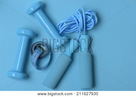 Dumbbells And Skipping Rope In Cyan Color On Blue Background
