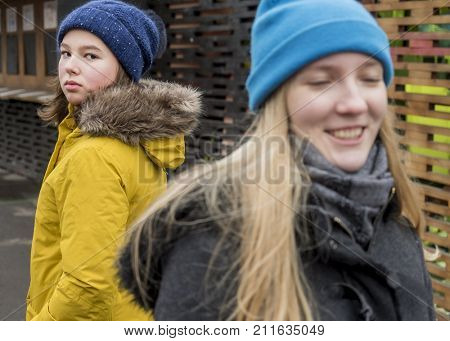 Envy. A teenage girl looks after her smiling girlfriend