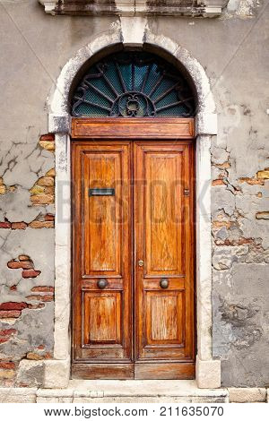 Beautiful vintage wooden door on an old wall with exposed bricks