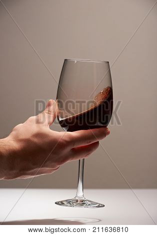 Elegant hand with red wine glass. Testing winery background