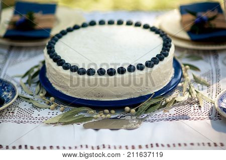 Cake with blue cream for men, decorated with blackberry and blueberry. Hands of Chef decorate the cake with berries. Selective focus.