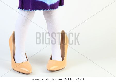 Little girl feet in high heel shoes. Close-up of child feet in mothers shoes on white background. Child has fun with mothers footwear. Funny kid background.