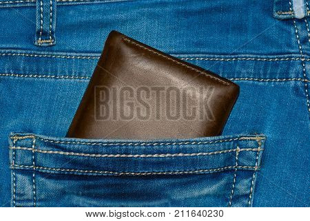 Brown leather purse in the pocket. Wallet halfway out from a jeans back. Pocket blue jeans with Wallet brown color