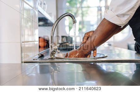 Chef Washing His Hands In Commercial Kitchen