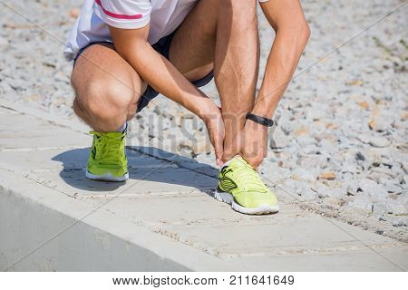 Running athlete feeling pain after having his leg injured. Accident on running track during the morning exercise. Sport accident concepts