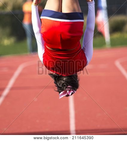 A high school cheerleader doing a flip during a time out of the football game.