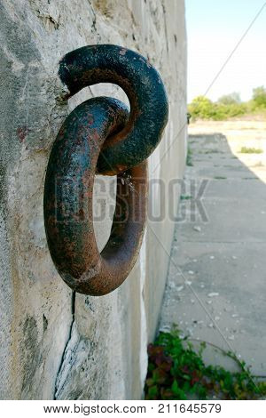 Old Metal ring shackle on concrete wall rusting