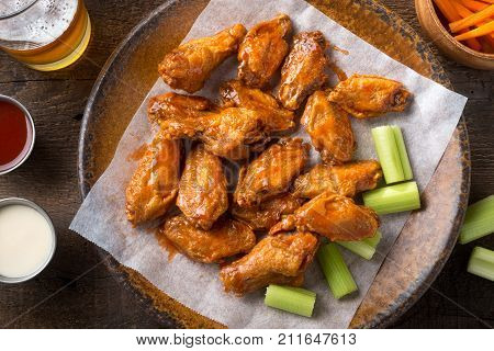 Delicious spicy buffalo chicken wings with beer celery carrot sticks and dipping sauces.